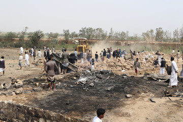 People gather as a bulldozer removes debris of a house to recover a missing woman at the site of a Saudi-led air strike on an outskirt of the northwestern city of Saada