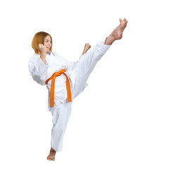 A girl strikes with a kick forward on a white background