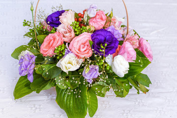 Summer flowers bouquet in a basket, white red and purple.
