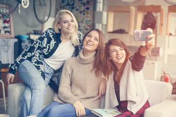 Three best friends in a cafe. Young women making self-picture.