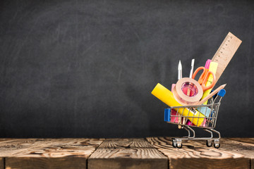 School Desk, Pencils And Various Supplies In Metal Shopping Holder On Blackboard Background