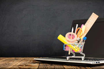 School Desk, Pencils And Various Supplies In Metal Shopping Holder On Laptop With Blackboard Background