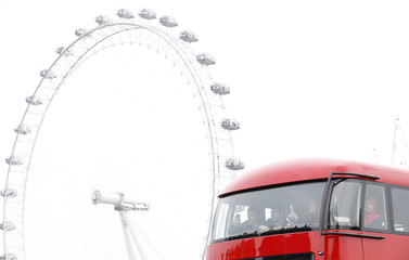People take pictures on the top deck of a bus as it passes the London Eye on Westminster Bridge as it is re-opened after an attack in London