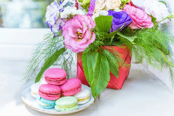 Summer flowers bouquet in a basket, white red and purple. Pink and green macaroons sweets and candies on white plate