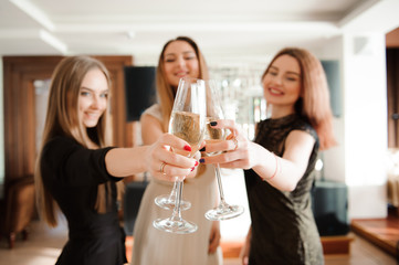 Portrait of smiling friends holding glass of champagne while dancing at bar