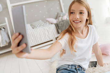 Excited little girl taking selfies in her bedroom