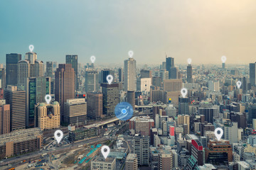 Searching location on map and pin above Osaka city and network connection, internet of things, satellite navigation system concept