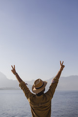 Italy, Lierna, back view of man standing in front of lake showing victory signs
