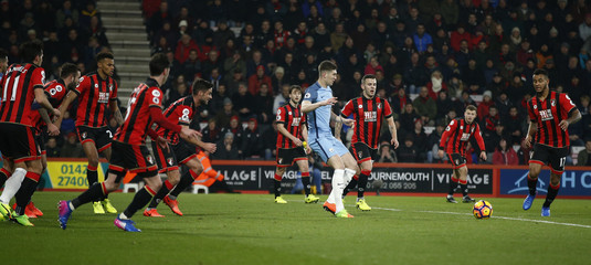Manchester City's John Stones in action with Bournemouth's Jack Wilshere and teammates