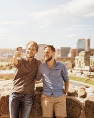 Happy young caucasian buddies making selfie at city skyline