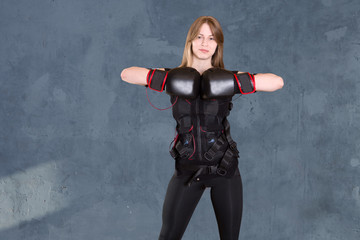 the young woman in a suit for EMS of a training. Fit girl exercise in the gym.