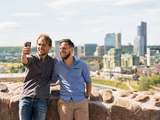 Smiling young caucasian buddies making selfie in front city skyline