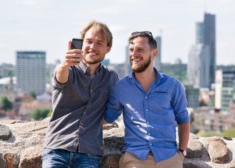Smiling young caucasian friends making selfie at city skyline