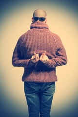 Bald man in a sweater, jeans and sunglasses with his back showing the middle finger. Toned