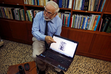 Doctor and historian Ibrahim Khalil Al-Allaf refers to Agatha Christie picture during the interview with Reuters in Mosul