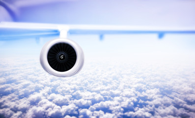 Airplane flight. Airplane engine and wings on the blue sky and white clouds. jet engine. flying above clouds, travel and vacation concept