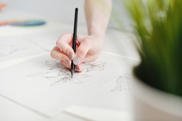 Young female illustrator working on sketches at home office