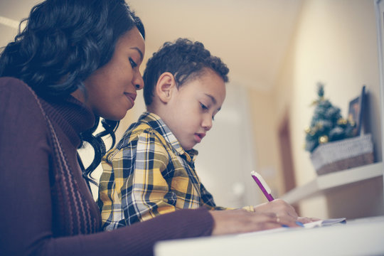 Time for educating. African American boy writing at home with his mother.