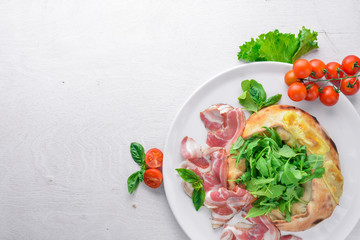 Salad with meat and vegetables. Italian cuisine. On a wooden background. Top view. Free space for your text.