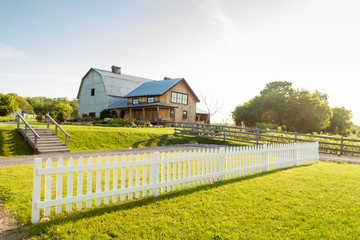 White picket fence and farmhouse