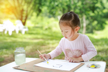 Happy asian child girl sitting at a table in a summer garden painting with paintbrush, Education art concept.