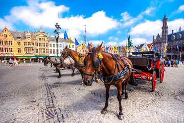 Stores photo Bruges Horse carriages on Grote Markt square in medieval city Brugge at morning, Belgium.