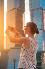 Young girl making picture of business center at sunset