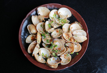 Fried Clams with spicy in plate on black table, Top view.