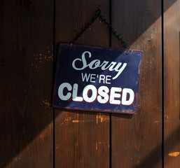 Sorry we're closed, blue and white retro sign on old wooden door, with a shadow that divides it into a clear and dark part