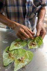 Man making betel nut on the street stall in Myanmar (Burma).