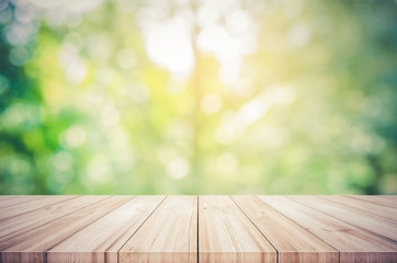 Empty wooden table top with blurred green natural abstract background.