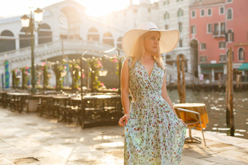 Woman tourist travel in Italy. Young girl with a white hat in venice on an old street. Girl traveling to Venice.