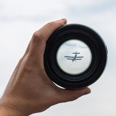 View through spyglass lens to the small airplane in the sky