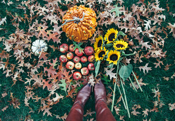 Person in boots standing above a fall scene with pumpkins, apples, sunflowers and leaves