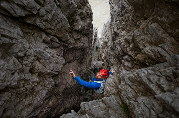 Alpinist rock climbing up a chimney crack outdoor
