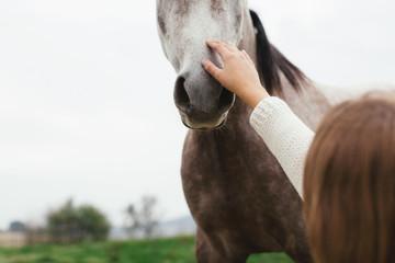 Teen girl with her horse on a farm.