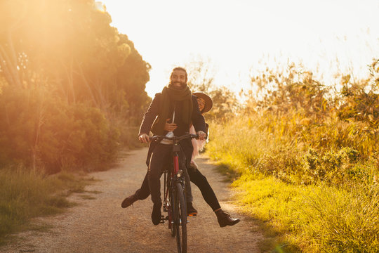 Young hipster couple riding a bicycle in the forest.
