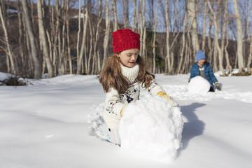 Children rolling a big snowballs.
