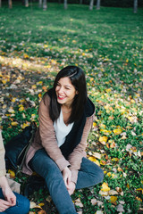 Beautiful brunette woman laughing in park sitting on grass