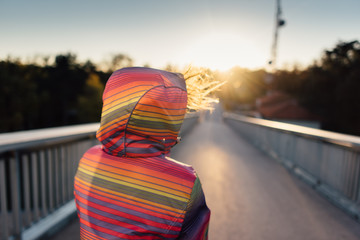 Back portrait of woman in colorful jacket against the sunset