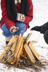 Close-up of couple warming themselves at fire
