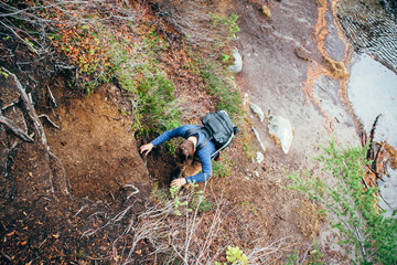 Young Man Climbing Down Dirt Slope Covered In Roots