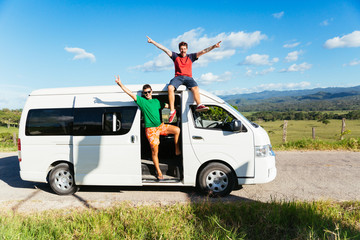 Two excited young men saluting from their white minivan during a break stopover in the middle of the road in the countryside