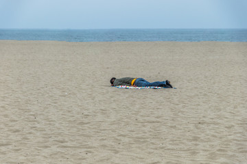 Homeless man taking a nap on the beach