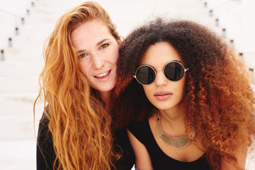 Redhed freckled woman with her afro friend