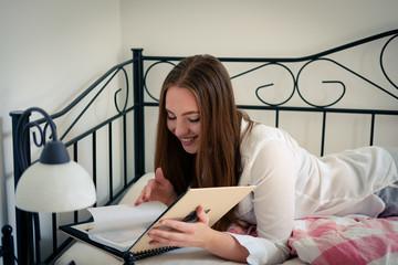 Junge Frau mit Fotoalbum im Bett