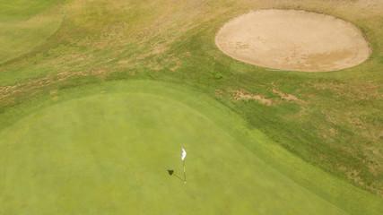 Vista aerea della buca finale del percorso di un campo di golf. Il prato fa parte di un ampio e ricco circolo di golf italiano frequentato dai migliori giocatori del panorama sportivo.