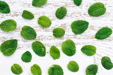 Mint leaves on a white wooden background