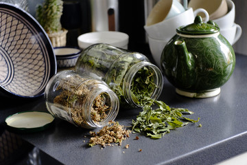 Close-up of herbs fallen from jars on table