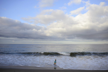 Girl playing in sea at Laguna Beach against cloudy sky